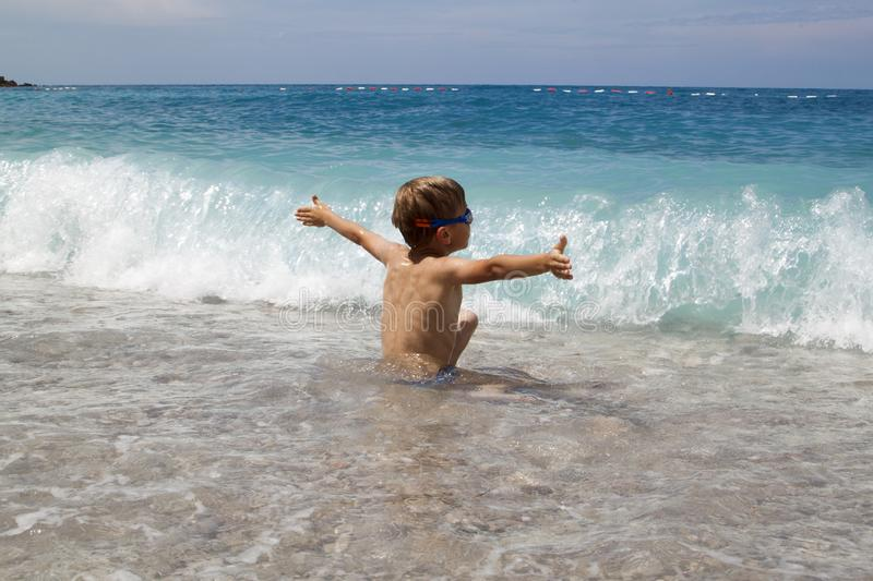 kid play with splahes waves of the sea royalty free stock photo
