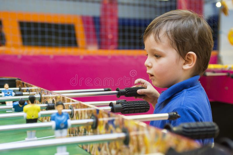Kid play table soccer. Hobby developing games. Little kid playing in children room royalty free stock images