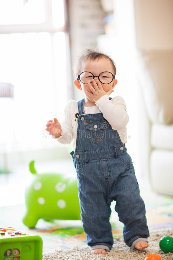 Kid playing. A kid wearing glasses on the floor playing royalty free stock images