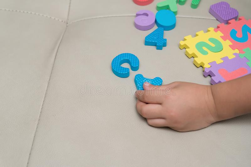 Kid playing alphabet jigsaw puzzles. On sofa royalty free stock photo