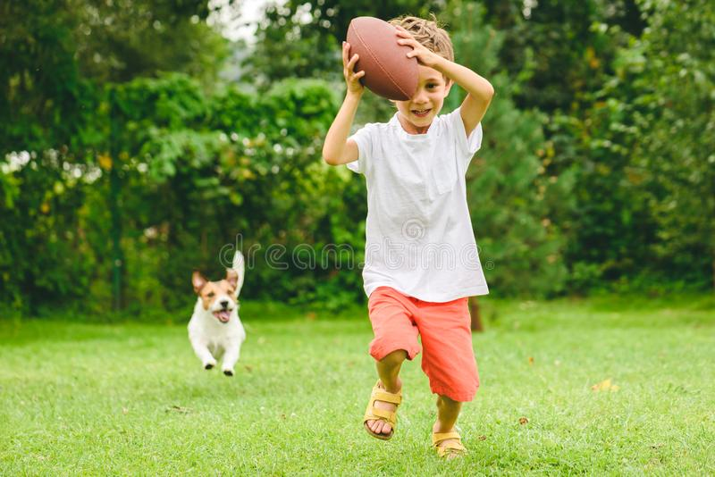 Kid playing american football ready to make touchdown and dog chasing him. Two friends having fun at backyard at sunny summer day stock image