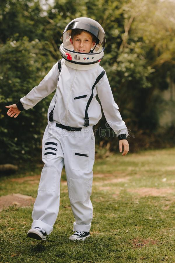 Kid playing in astronaut suit outdoors. Boy pretending to be an astronaut, wearing space suit and helmet royalty free stock photography