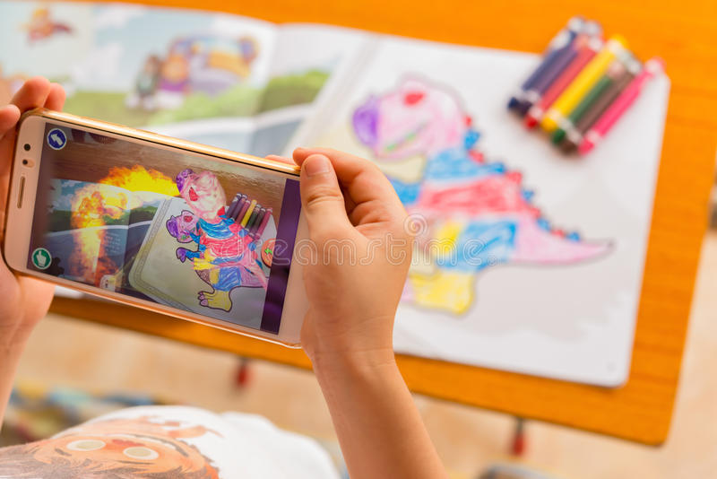 Kid playing Augmented Reality popup paintings of a filled dinosaur via mobile. Zhongshan,China-August 8, 2017:kid playing Augmented Reality popup paintings of a royalty free stock photography