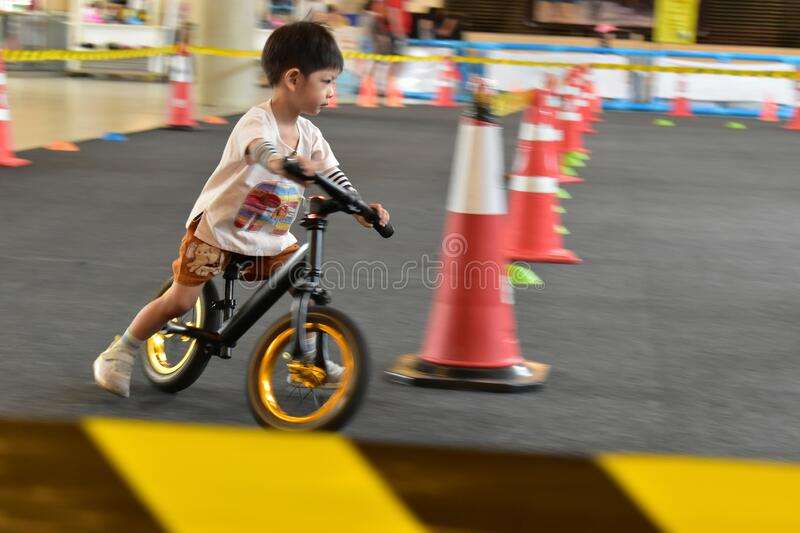 Kid playing balance bike in racetrack, speed motion blur royalty free stock photos