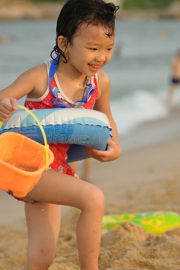 Kid playing on the beach stock photos