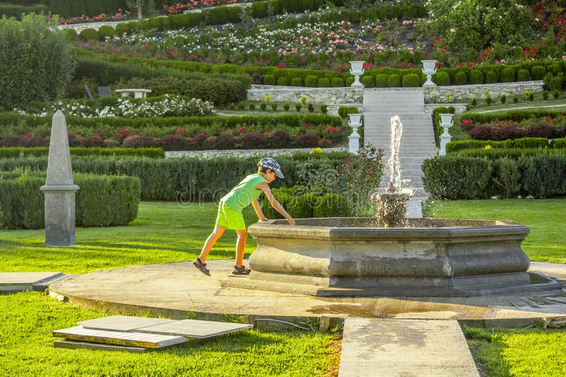 Kid playing in beautiful green garden. Kid playing in beautiful green garden with waliking alley, green grass and ornamental bushes stock photos