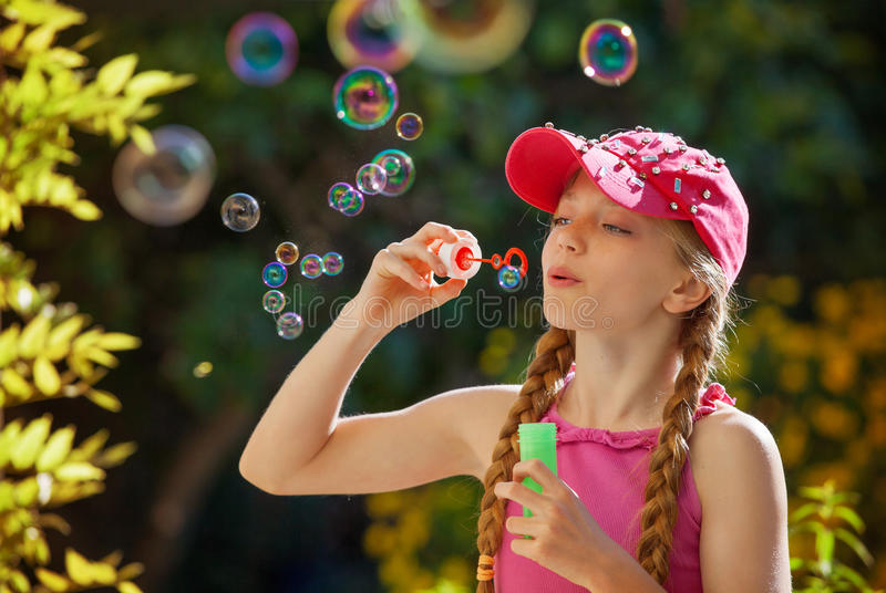 Kid playing with bubble pipe. Happy healthy summer kid playing with bubble pipe royalty free stock photography