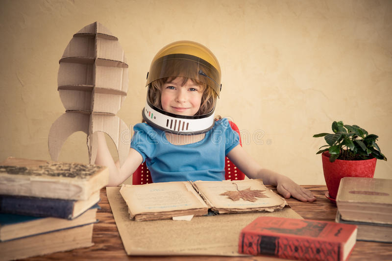Kid playing with cardboard toy rocket. Kid astronaut with cardboard toy rocket. Child playing at home. Earth day concept royalty free stock images