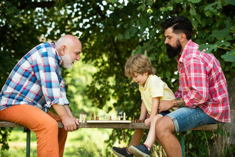 Kid Playing Chess. Handsome grandpa and grandson are playing chess while spending time together outdoor. Happy man royalty free stock photos