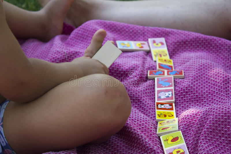 Kid playing dominoes. With mother on the park royalty free stock image