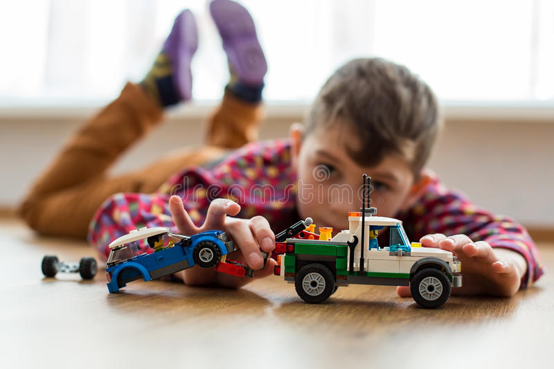 Kid playing on the floor. Boy plays with toy cars. Kid playing on the floor. Child's daytime fun. Happy to be at home stock photo