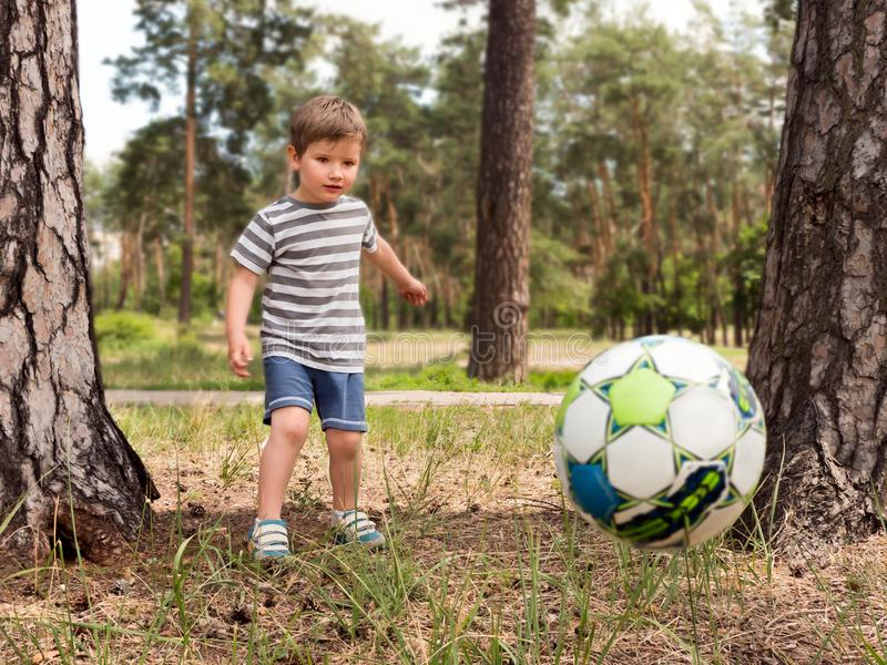 Kid playing football soccer at grass city park field running and kicking the ball excited in childhood sport passion and. Young little kid 4 or 5 years old stock photography