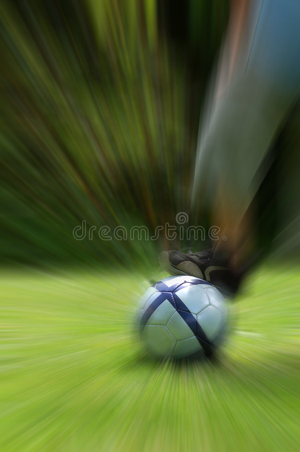 Kid playing football (soccer) - zooming effect (ball and foot sharp) stock photos