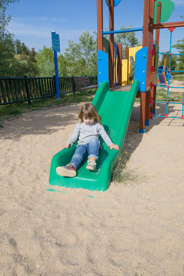 Kid playing in green slide stock image