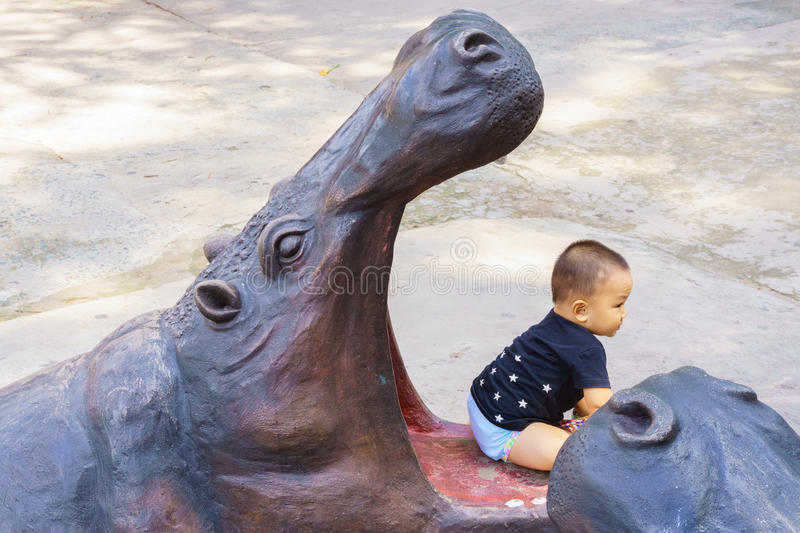 Kid playing with hippo statue. Ho Chi Minh, Vietnam – July 17 2015: The kid is sitting in mouth of hippo statue the Thao Cam Vien zoo park, Ho Chi Minh royalty free stock images