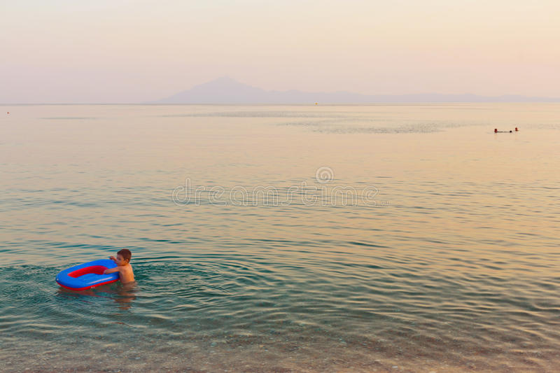 Kid playing with inflatable boat. Kid playing after sunset with inflatable boat in sea water royalty free stock photography