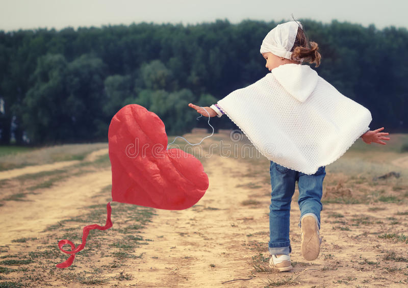 Kid girl playing with a red heart kite. Lovely little girl playing with red heart kite