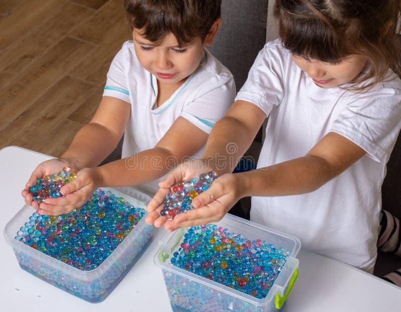 Kid playing orbeez. Orbeez balls - sensory water beads. stock photos