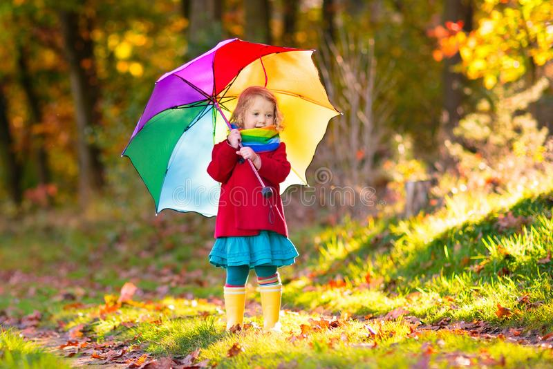 Kid with umbrella playing in autumn rain royalty free stock photography