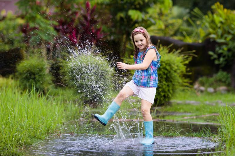 Kid playing out in the rain. Children with umbrella and rain boots play outdoors in heavy rain. Little boy jumping in muddy puddle royalty free stock image