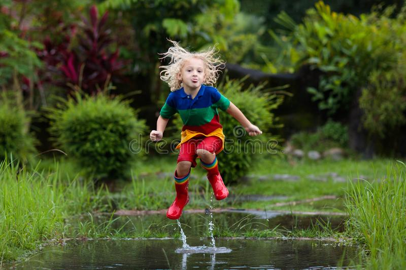 Kid playing out in the rain. Children with umbrella and rain boots play outdoors in heavy rain. Little boy jumping in muddy puddle stock images