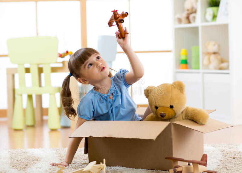 Kid playing with plane toy at home. Travel, freedom and imagination concept. stock photo