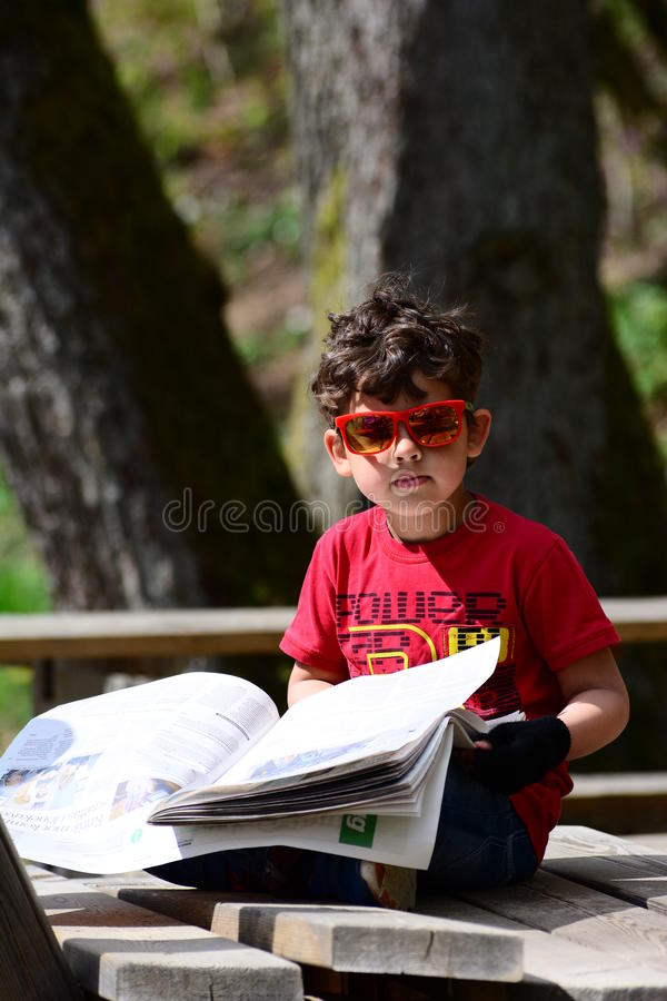 Kid playing. Kid pretend to read the newspaper stock image