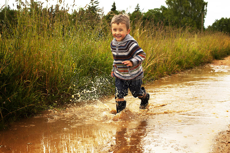 Kid playing in puddle royalty free stock photography