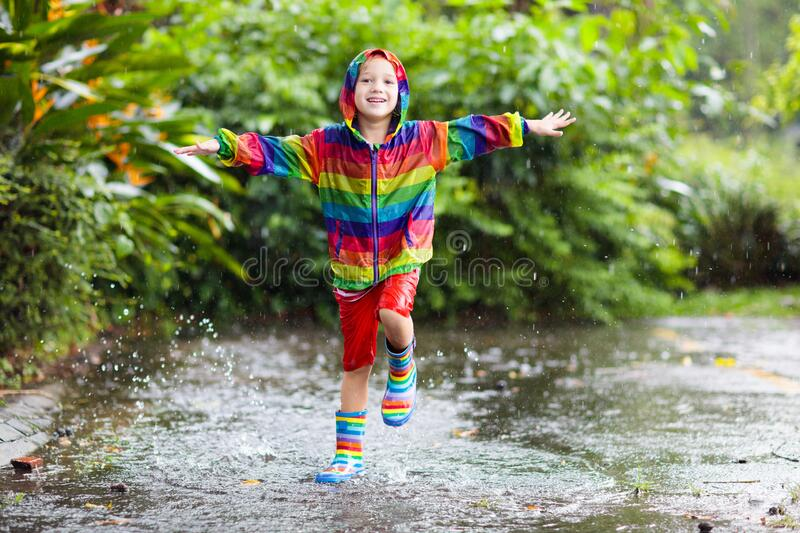 Kids in puddle in autumn rain. Waterproof wear royalty free stock photos