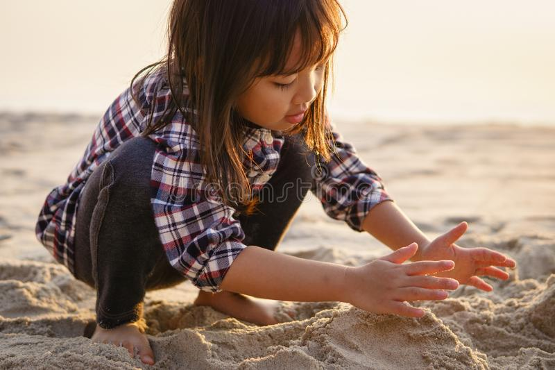 Kid playing sand at the beach stock photos