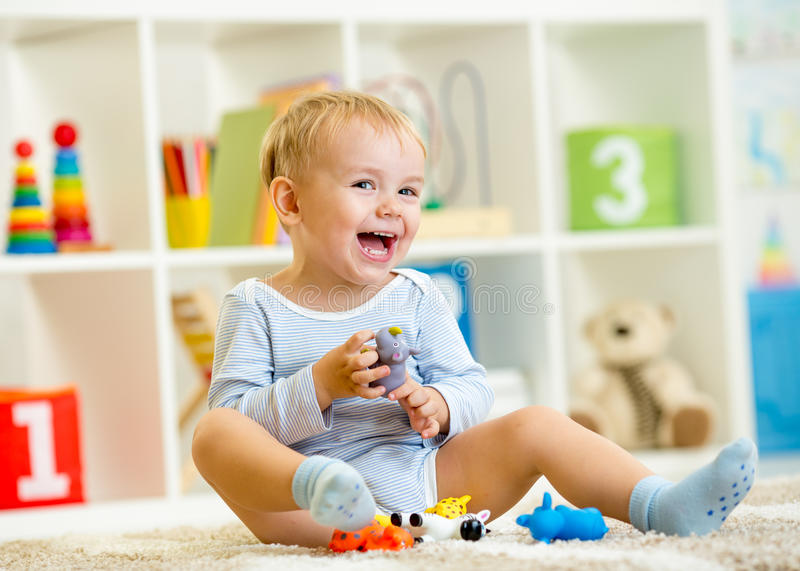 Kid playing with toy animals indoors. Kid boy playing with toy animals indoors royalty free stock photo