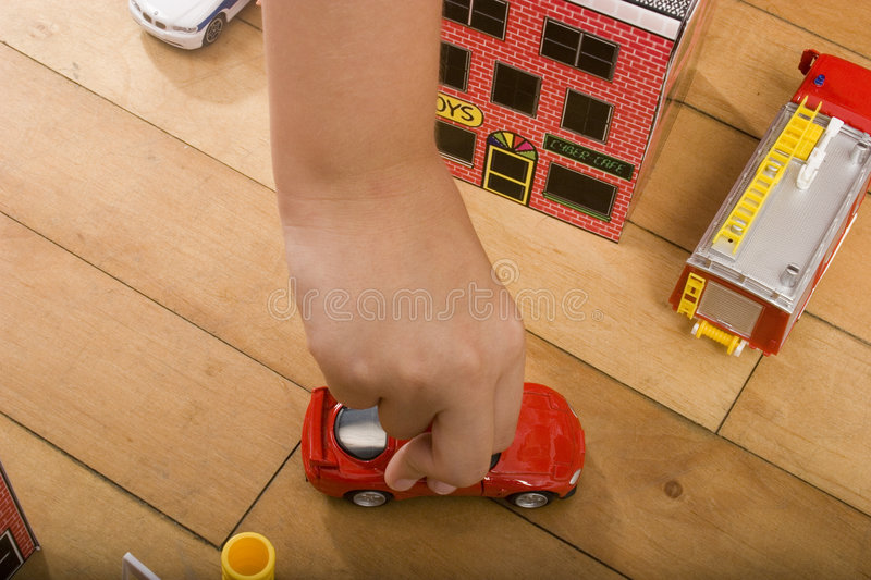 Kid playing with toy car. A kid playing with a toy car on a wooden floor, pretending to drive the car by using his hand to steer it royalty free stock image
