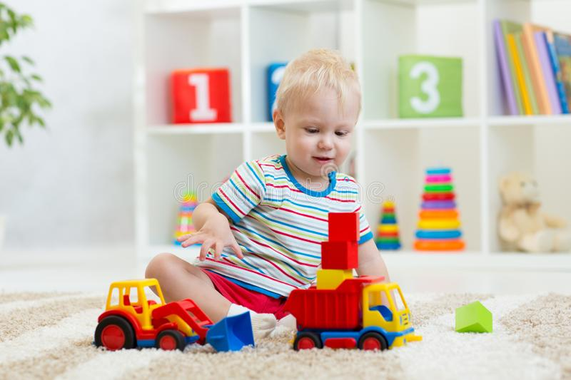 Kid playing toy cars at home or kindergarten royalty free stock images
