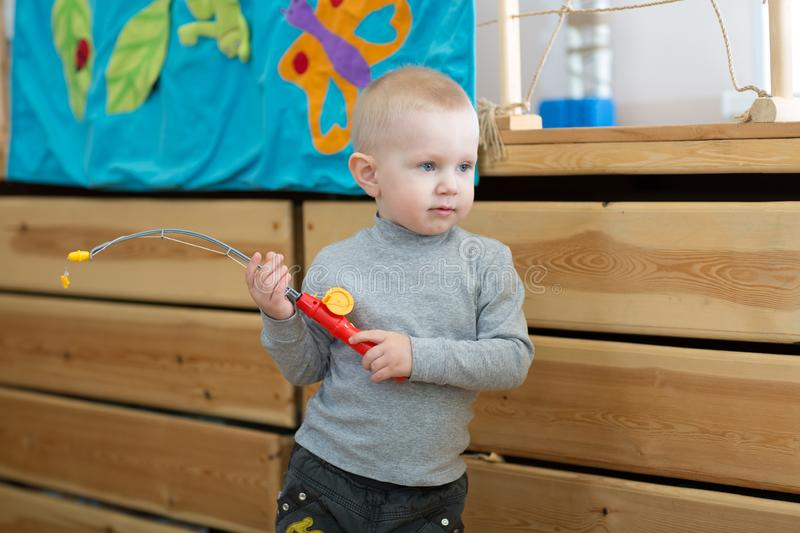 Kid playing toy rod in kindergarten or daycare centre. Boy playing with toy rod in kindergarten or daycare centre royalty free stock photography