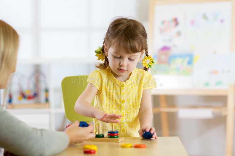 Kid is playing with toys in nursery stock photos
