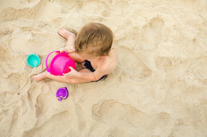 Kid playing with toys on sand royalty free stock images