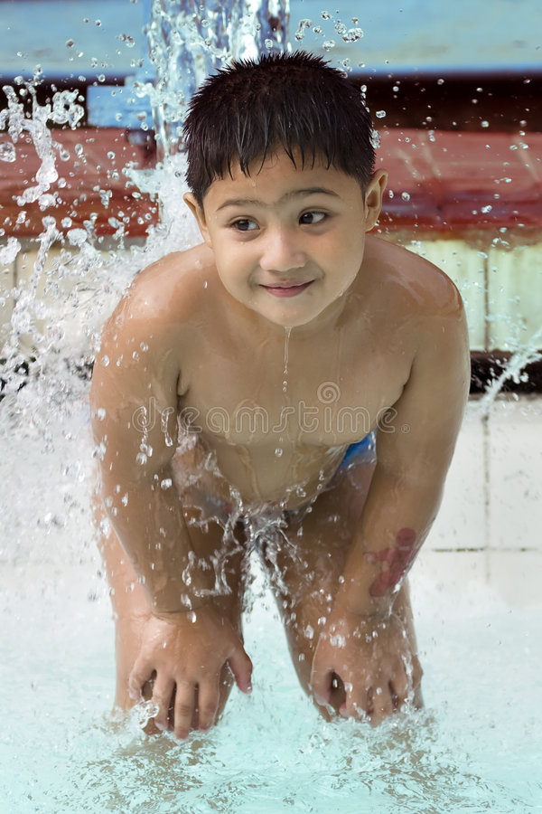 Kid playing with waterfountain. Kid playing with water fountain inside swimming pool stock photos