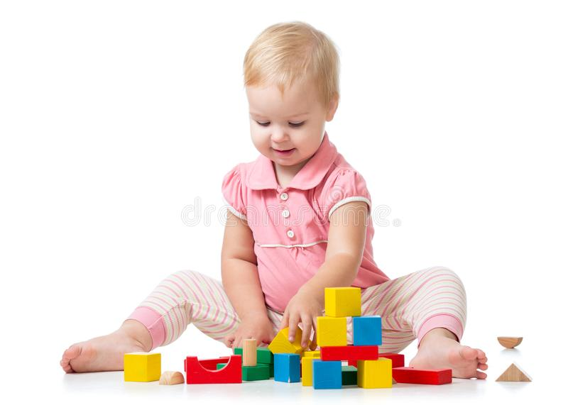 Kid playing with wooden block toys. Baby girl building castle using cubes. Educational toys for preschool and stock image