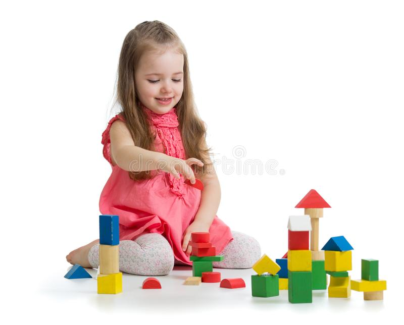 Kid playing with wooden block toys. Baby girl building castle using cubes. Educational toys for preschool and royalty free stock photography