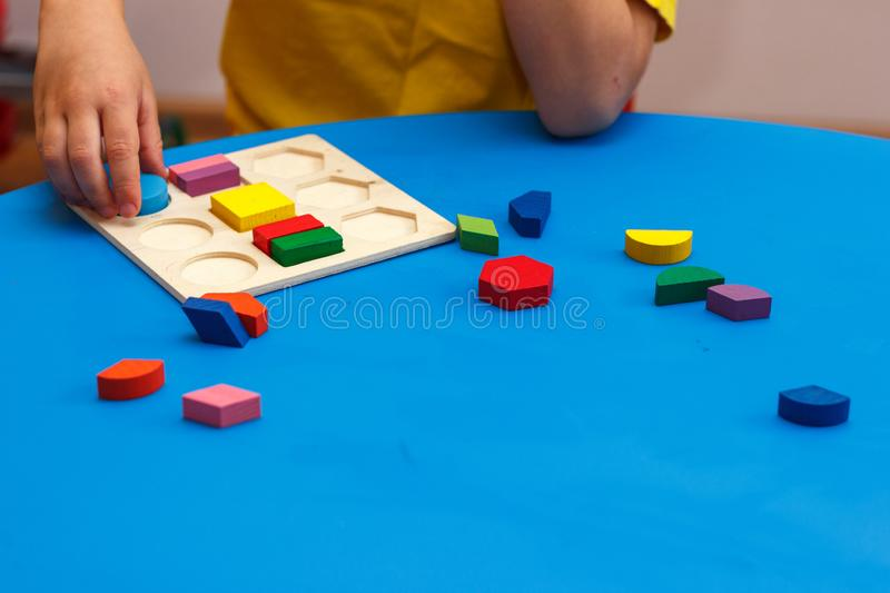 Kid playing with wooden colorful puzzle, education concept. Block, boy, challenge, childhood, collect, creative, game, geometric, geometry, kindergarten stock photos