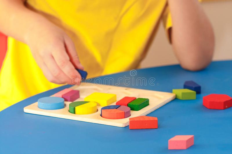 Kid playing with wooden colorful puzzle, education concept. Block, boy, challenge, childhood, collect, creative, game, geometric, geometry, kindergarten royalty free stock photos