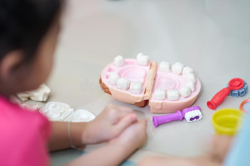 Kid plays on doh clay in dentist ,teeth and tools on floor stock photo