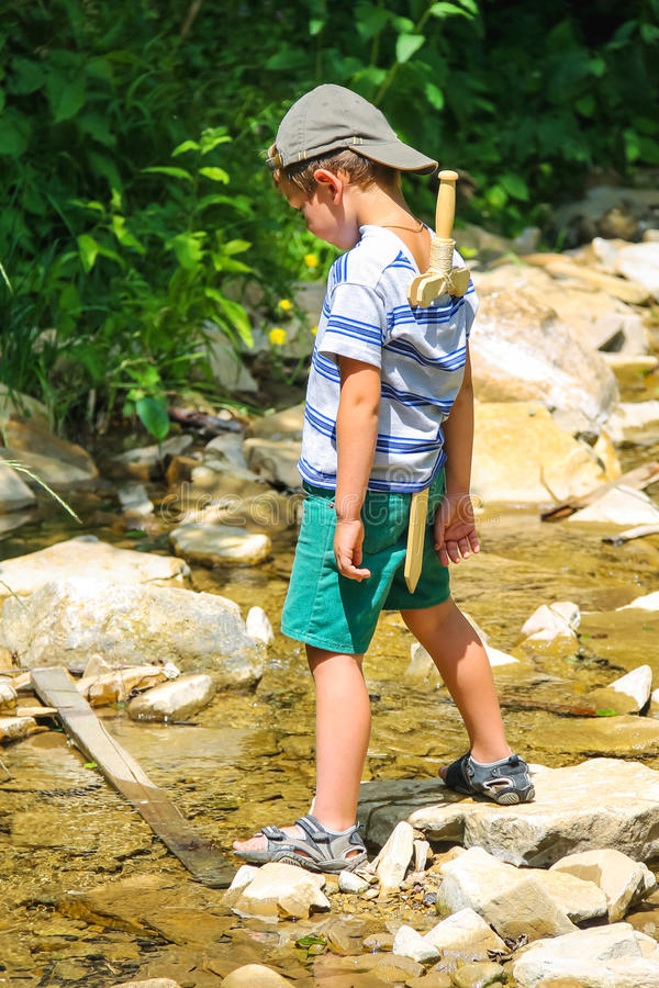 The kid plays near a mountain stream royalty free stock image