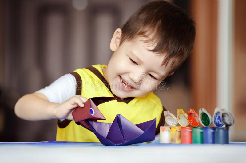 Kid plays sea battle, an origami figure Godzilla. Paper battle, an origami figure Godzilla attacks a paper boat, children's games. The development of imagination stock image