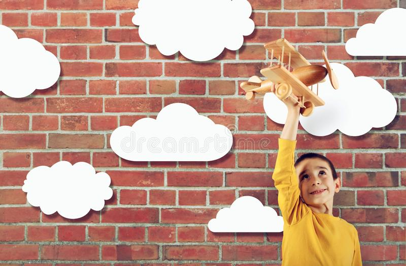 Kid plays with a wooden toy airplane stock images