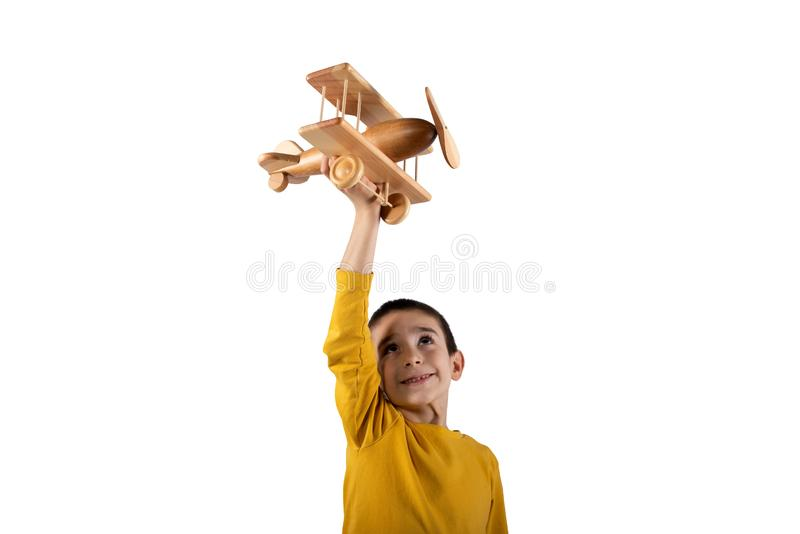 Kid plays with a wooden toy airplane. Isolated on white background stock photo