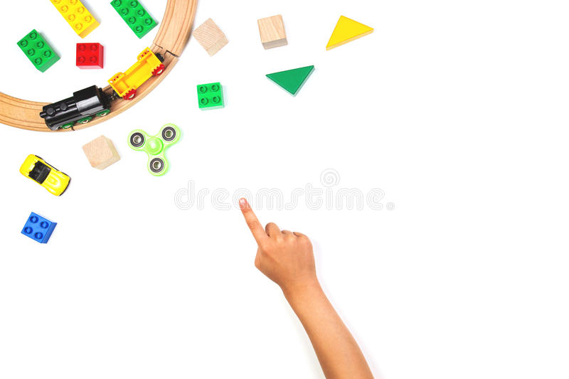Kid pointing finger to colorful toys. Fidget spinner, cars, toy train, bricks and blocks on white background. Child pointing finger to colorful toys. Fidget stock photo