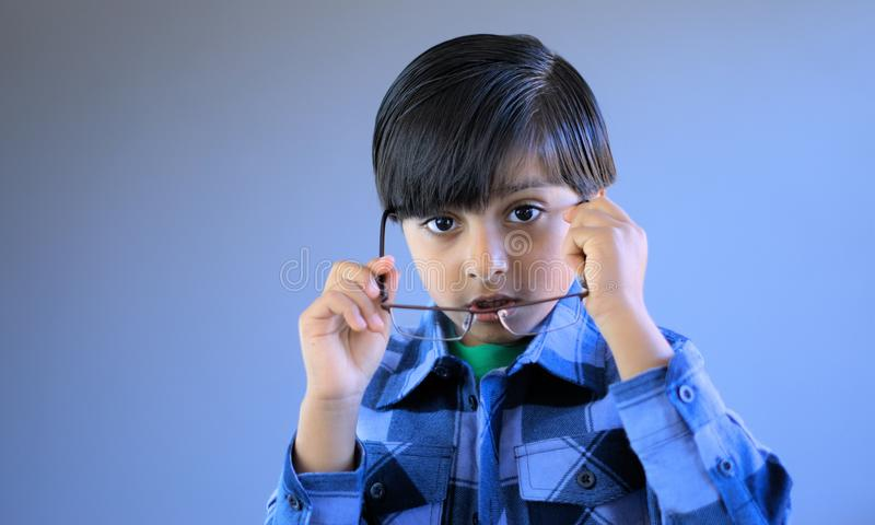 Kid putting eye glasses on. Child in act of wearing glasses. Subject looking at lens royalty free stock photo
