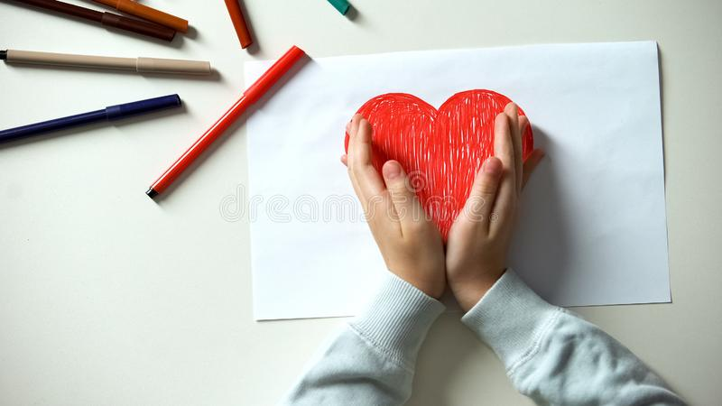 Kid putting hands on red heart picture, childhood and love, charity concept stock photo