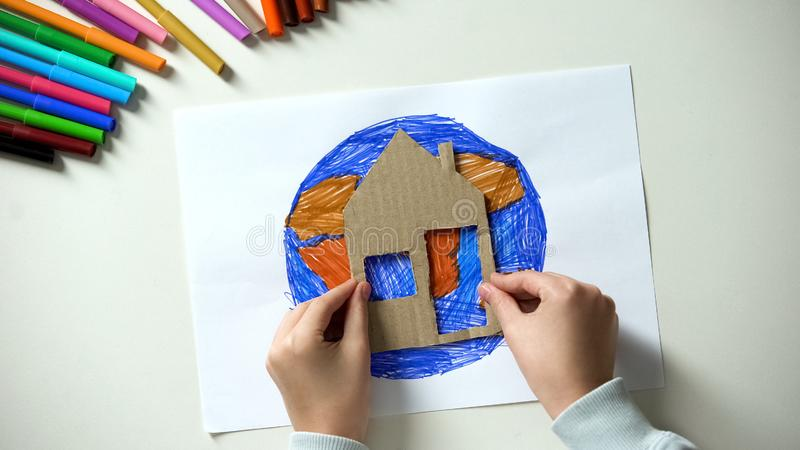 Kid putting paper house near Earth painting, world our home, saving planet royalty free stock images